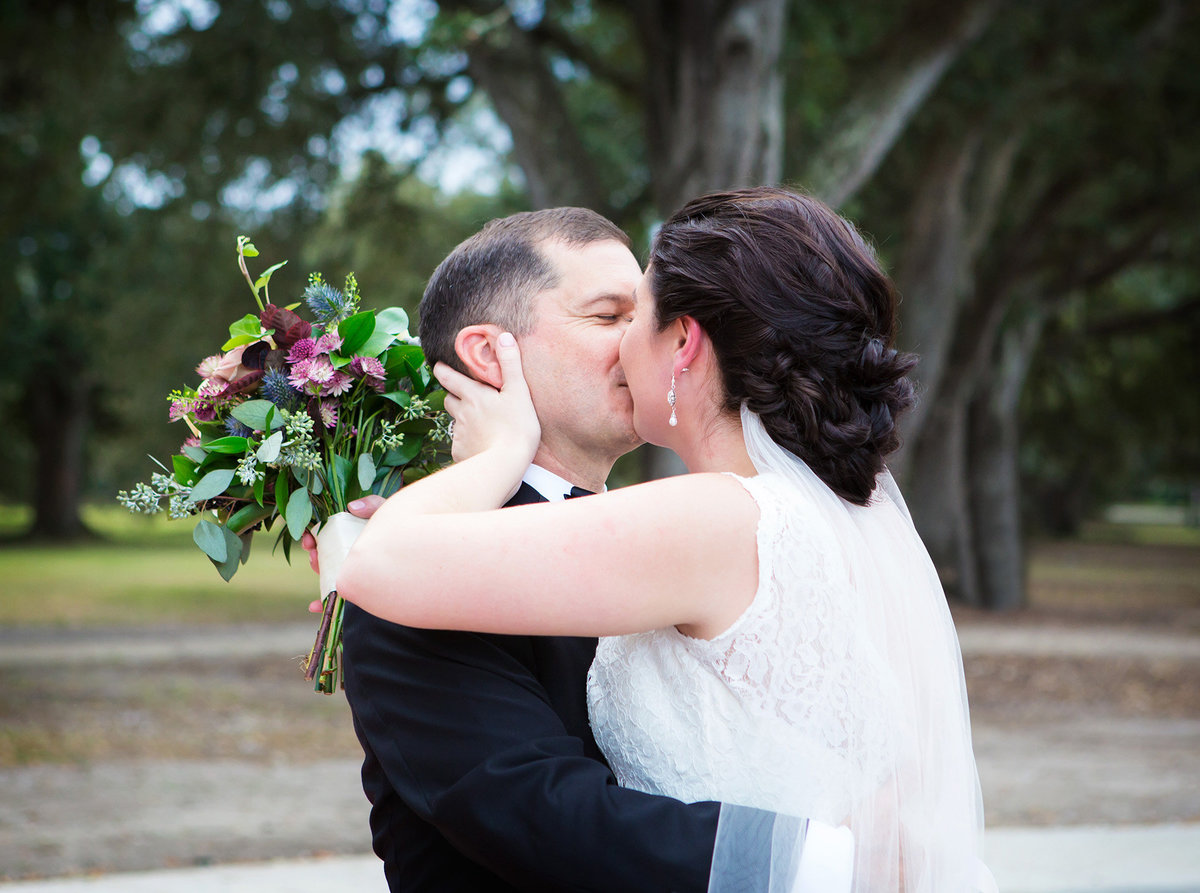 NOLA bride and groom kissing after just being married in Audubon Park