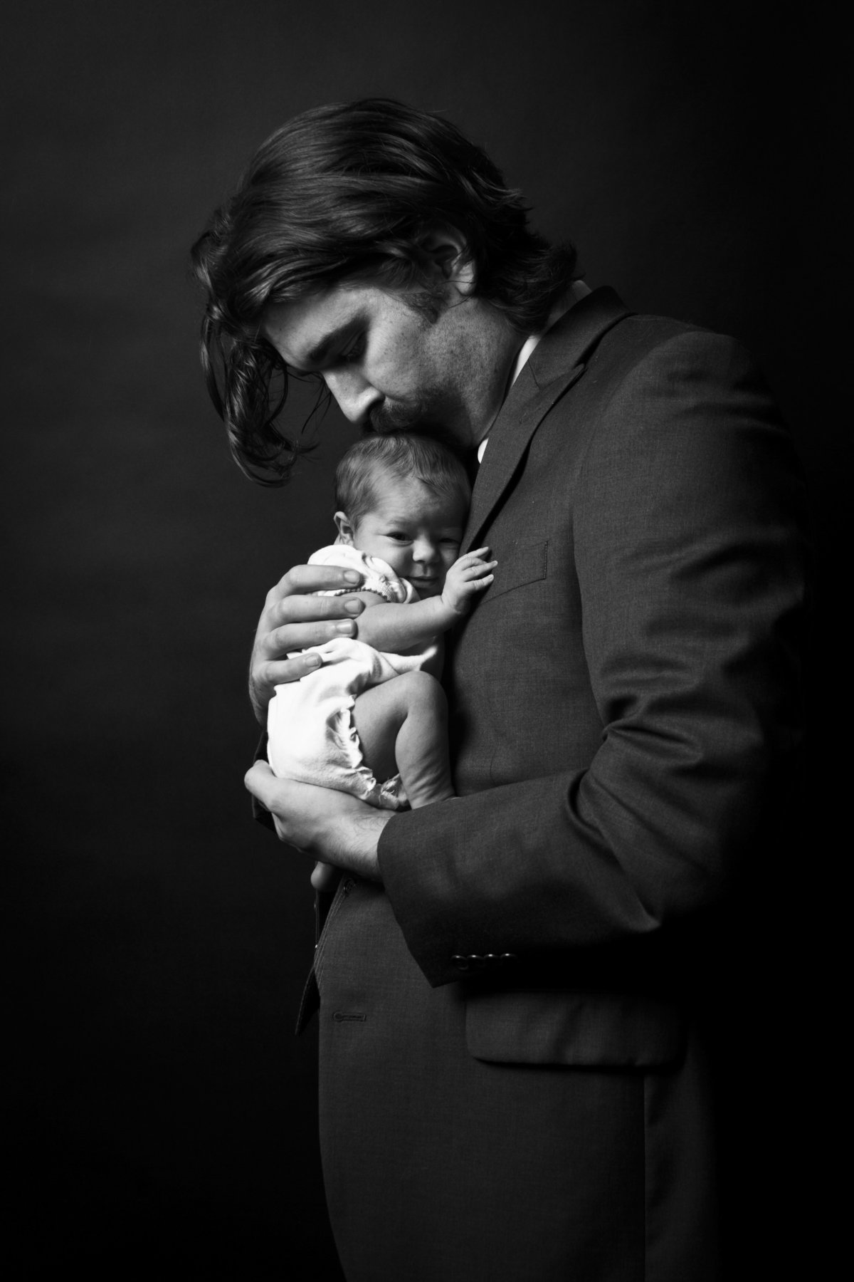 Father holding his newborn baby for and in home newborn photography session.