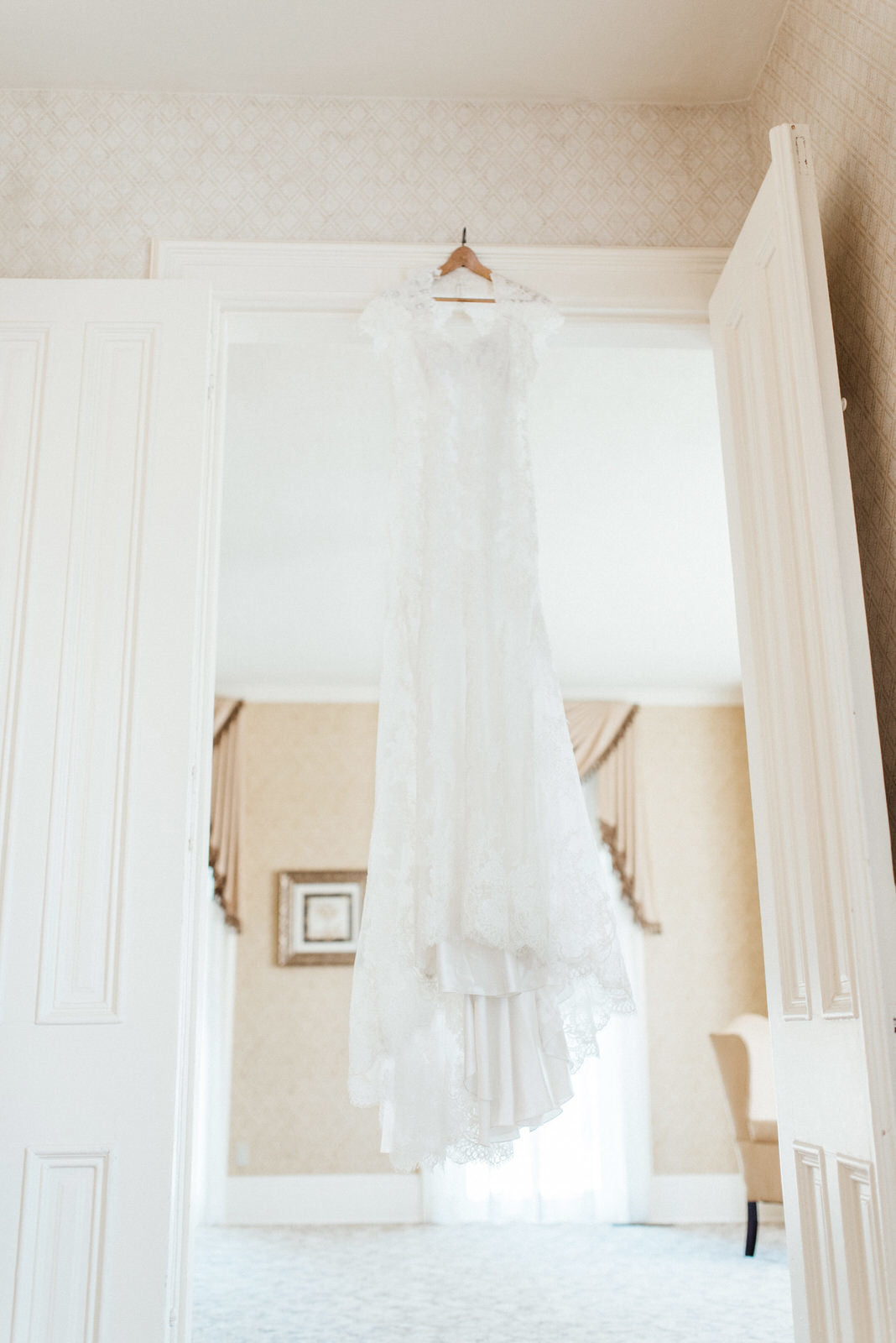 vintage wedding dress hanging in doorway