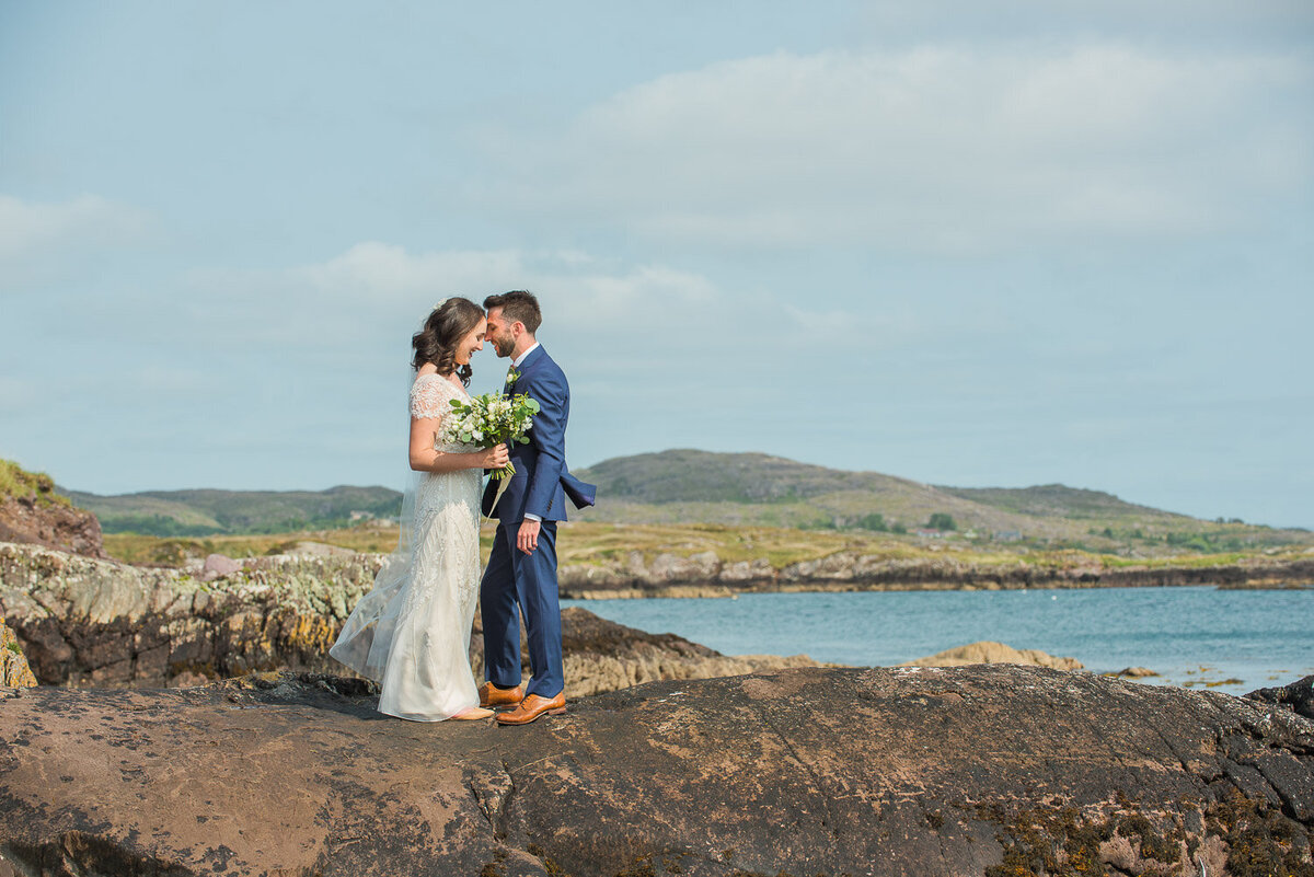 bride wearing a modified a-line, beaded wedding dress embracing her husband while standing on rocks overlooking Castlecove in Kerry