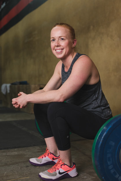 nutritionist at the gym sitting on barbell
