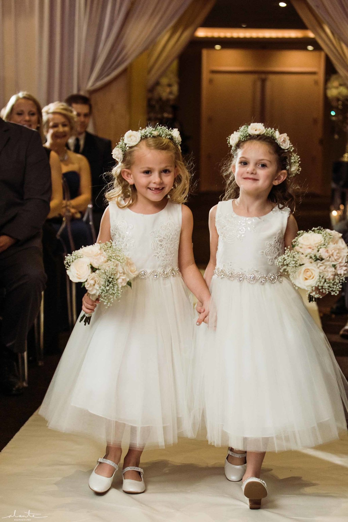 Darling flower girls with white flower crowns and small floral posies.