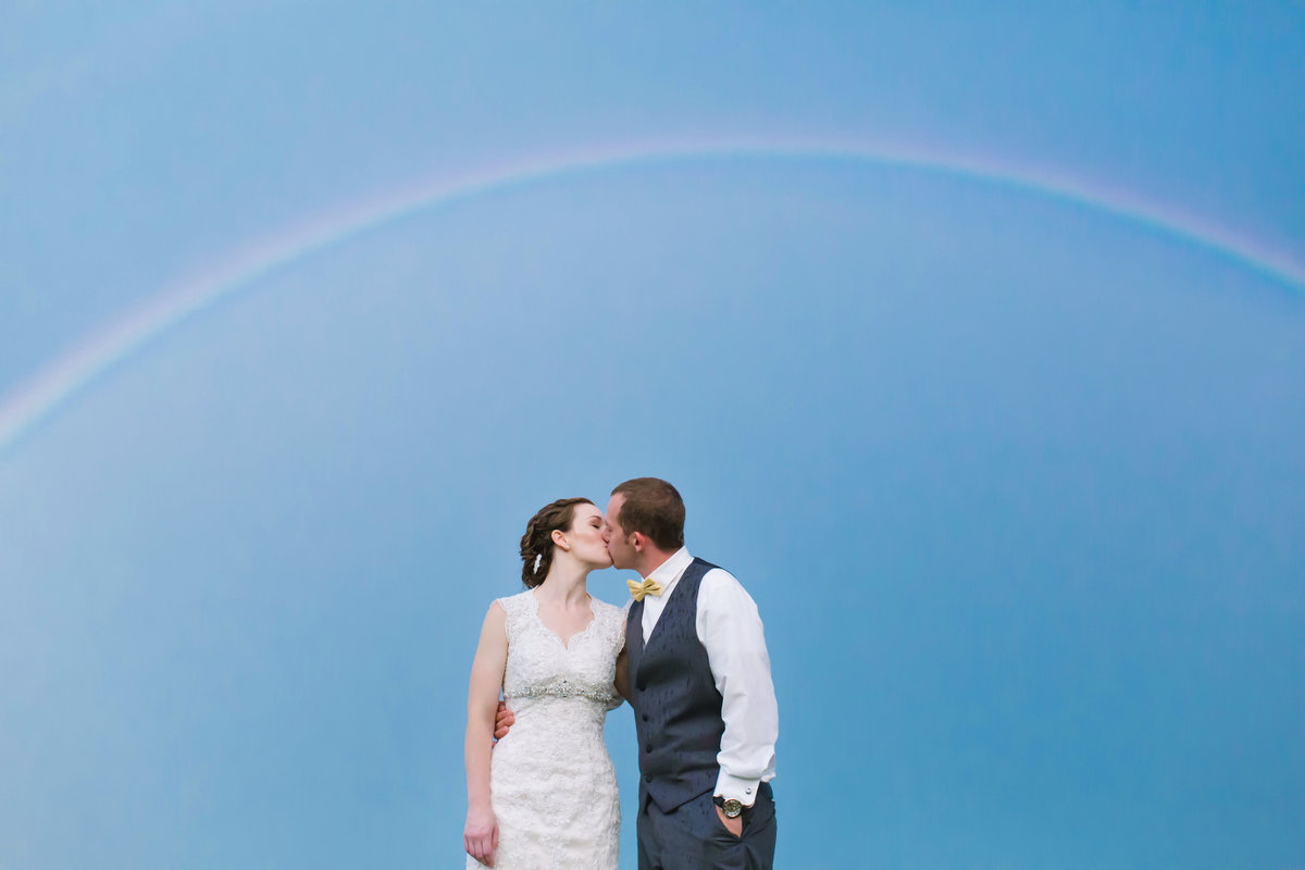 The bride and groom kiss under a rainbow at Veasey Park in Groveland Massachusetts