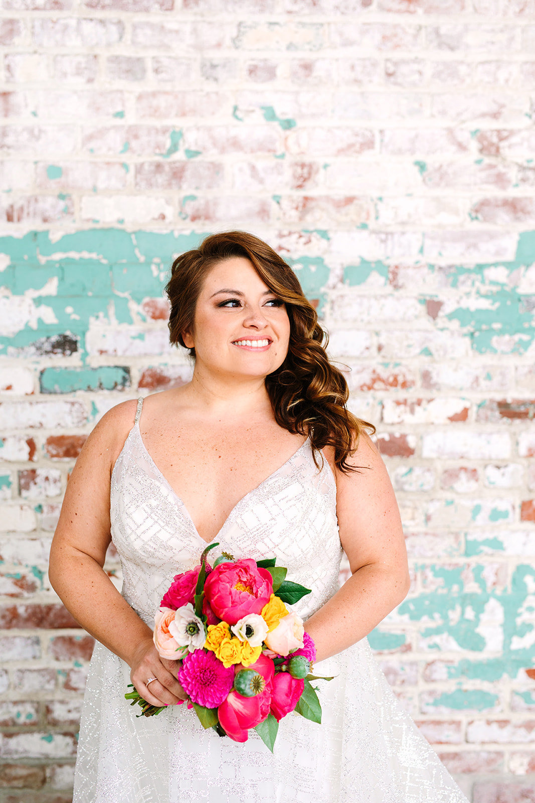 Bride with bright pink and orange bridal bouquet and spaghetti strap wedding dress at The Unique Space LA
