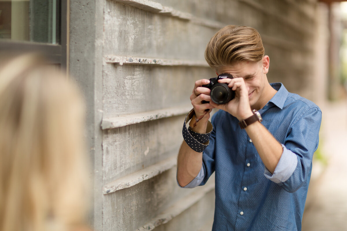 young man taking pictures with camera