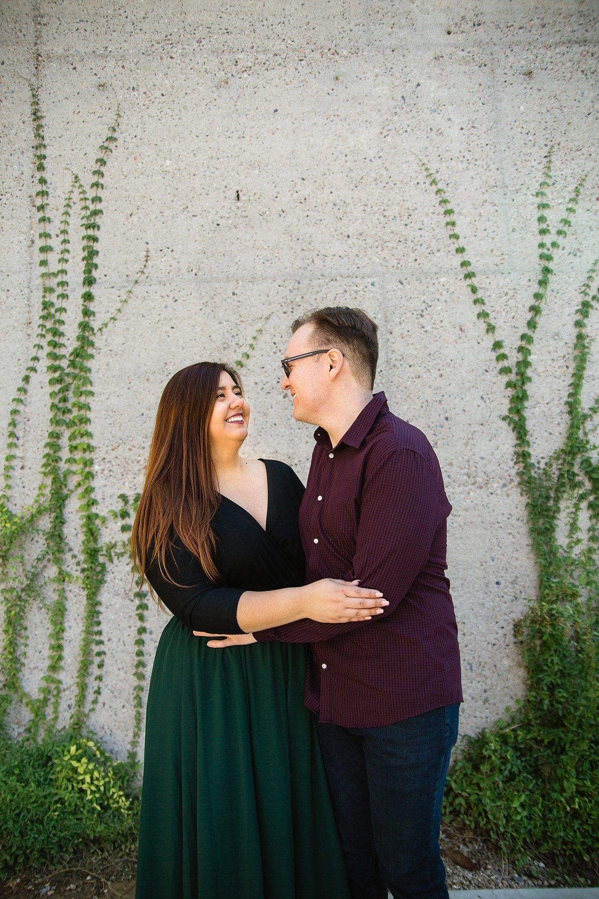 Couple smiling at each other during their Mesa Arts Center engagement session by PMA Photography.