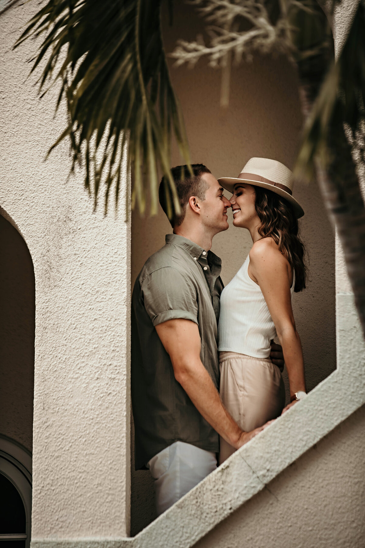 A picture of a couple marking their engagement at a vintage building, pausing to romantically gaze in each other's eyes as they stand close together by Garry & Stacy Photography Co - Tampa FL engagement photography