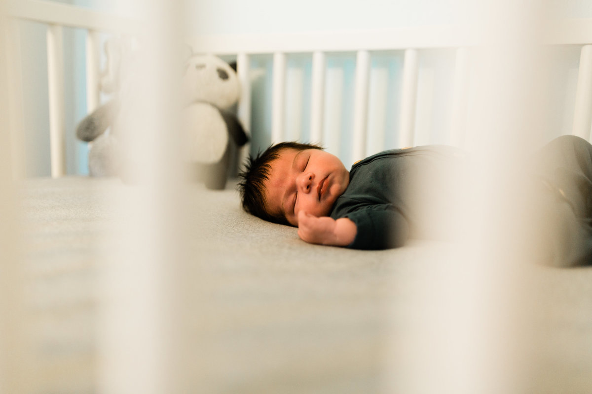 newborn baby boy sleeping in a crib