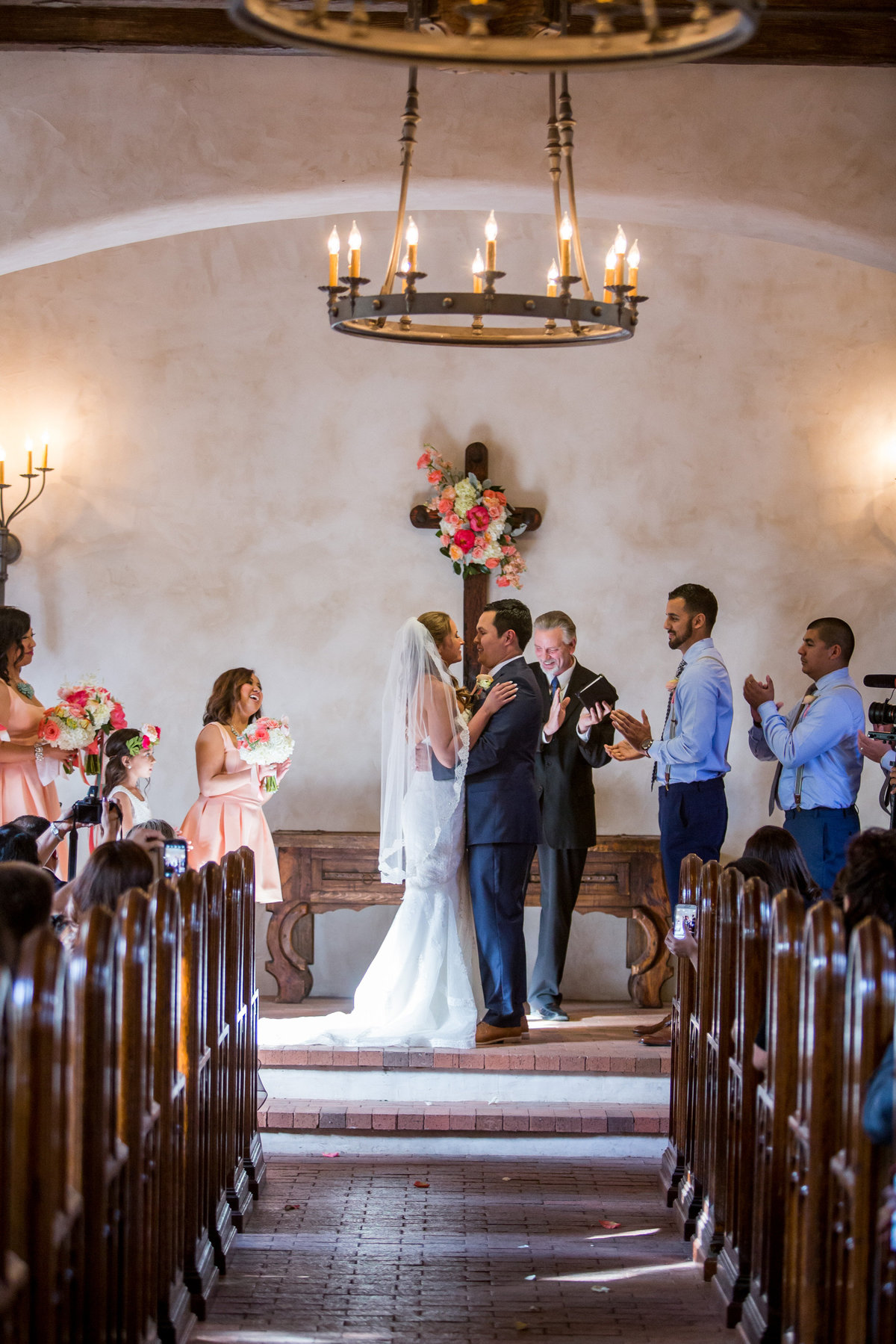 Bride and groom hold each other during wedding ceremony at Lost Mission venue in Hill Country