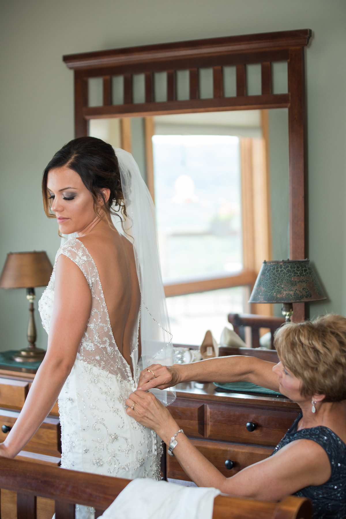 mother helping bride put on wedding dress