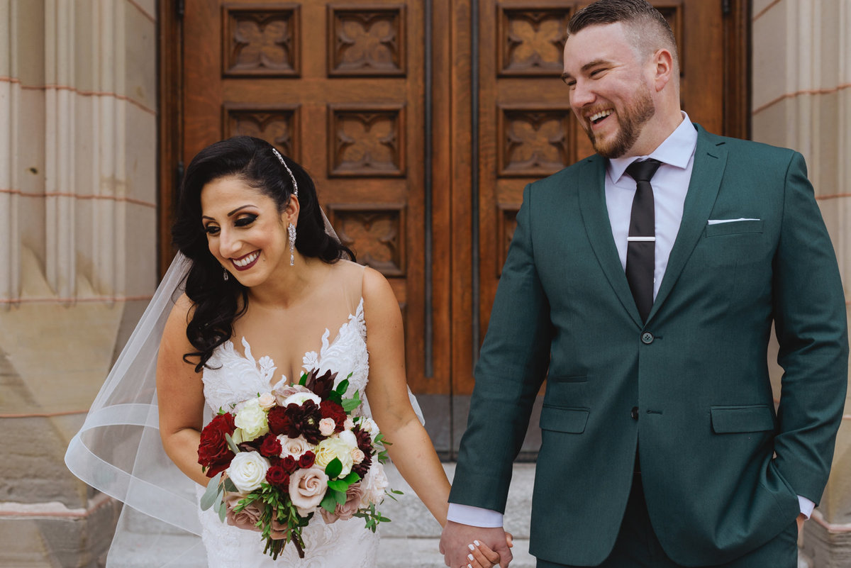 bride and groom laughing holding hands