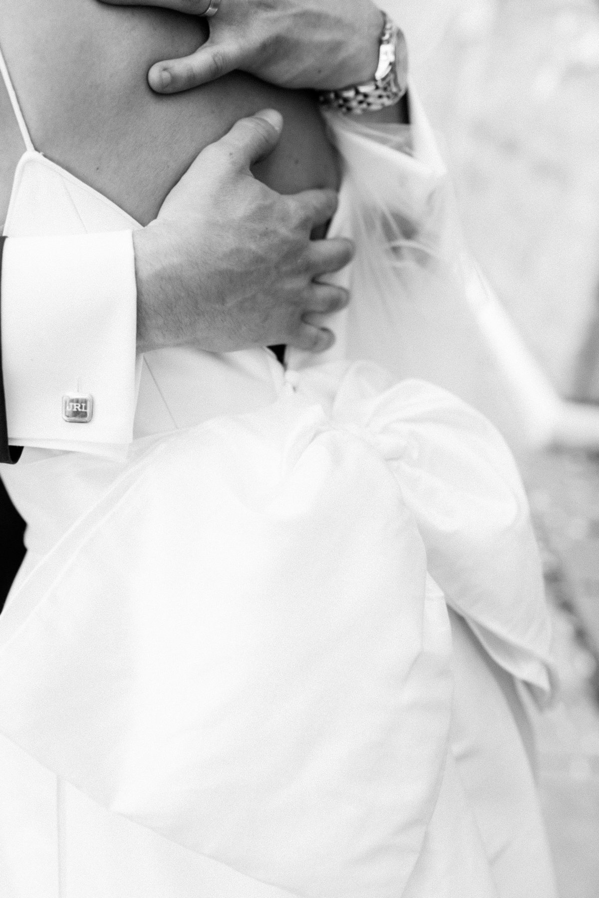 Close up of groom's hands as he hugs his new wife on their wedding day