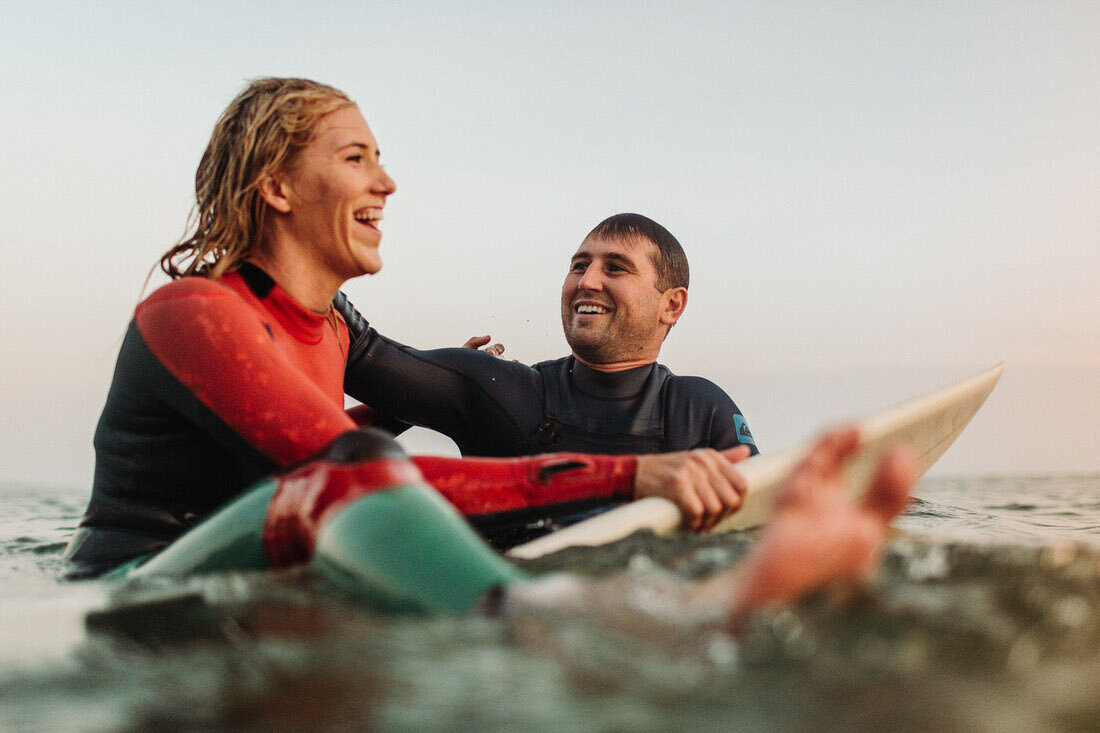 Couple paddles out to catch a wave together during their El Matador State Beach surf engagement session in Malibu, Ca.
