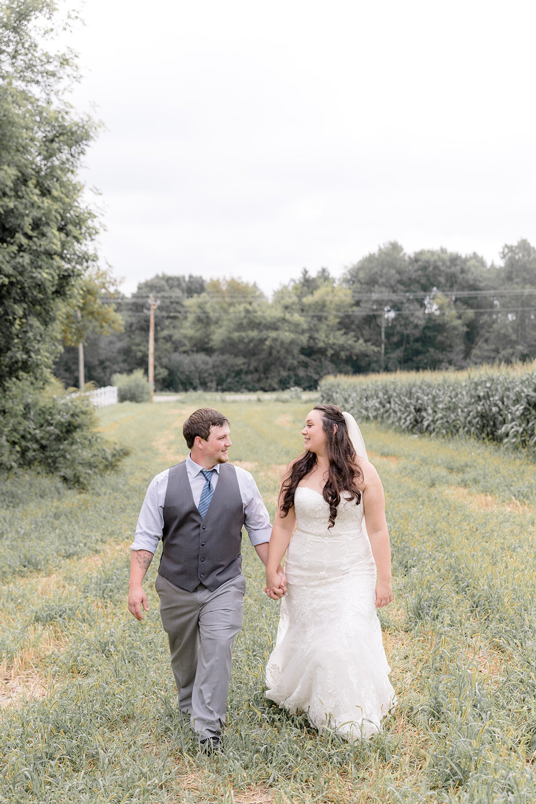 Bride and Groom Walk Holding Hands in Field Precott Wisconsin
