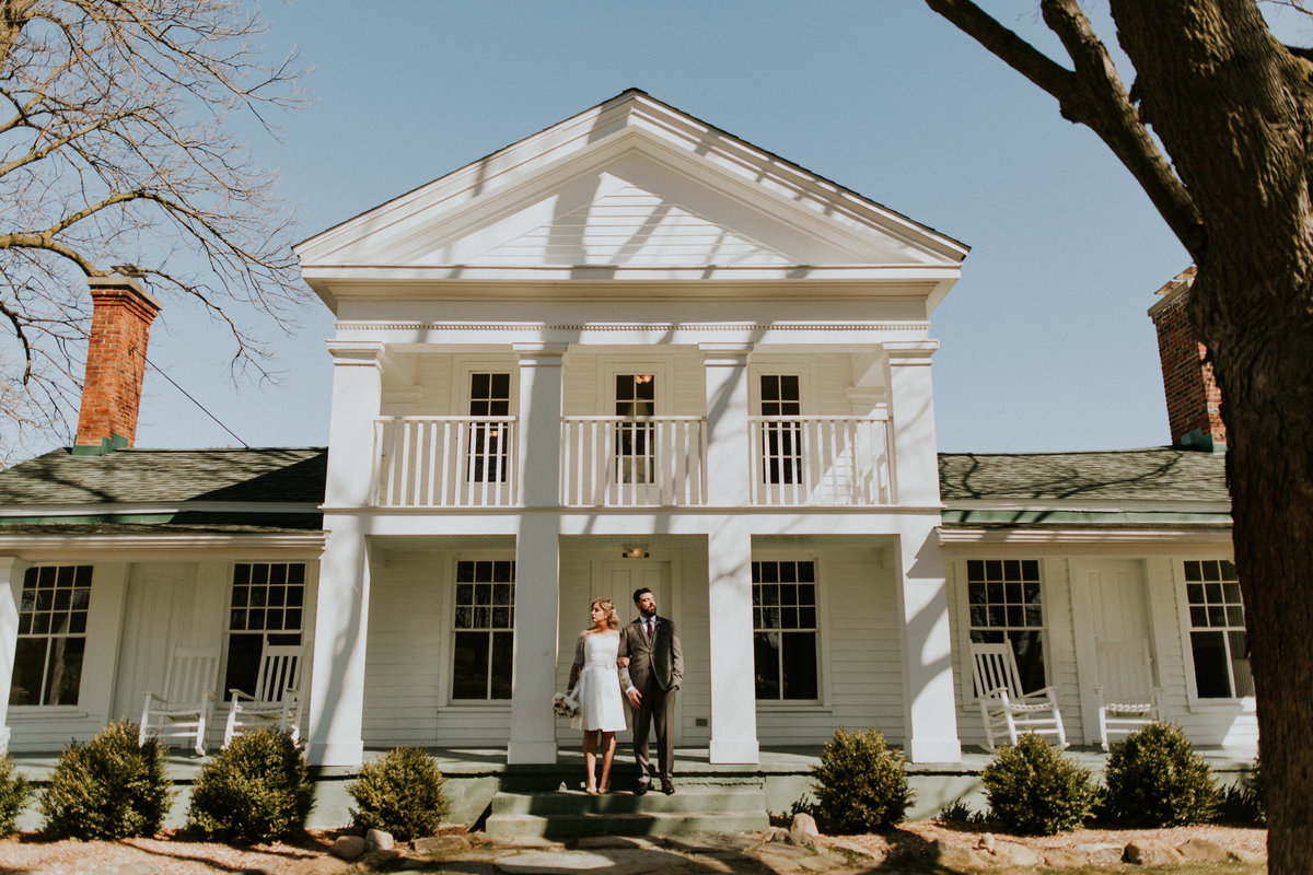 A bride and groom stand on the steps of the farmhouse