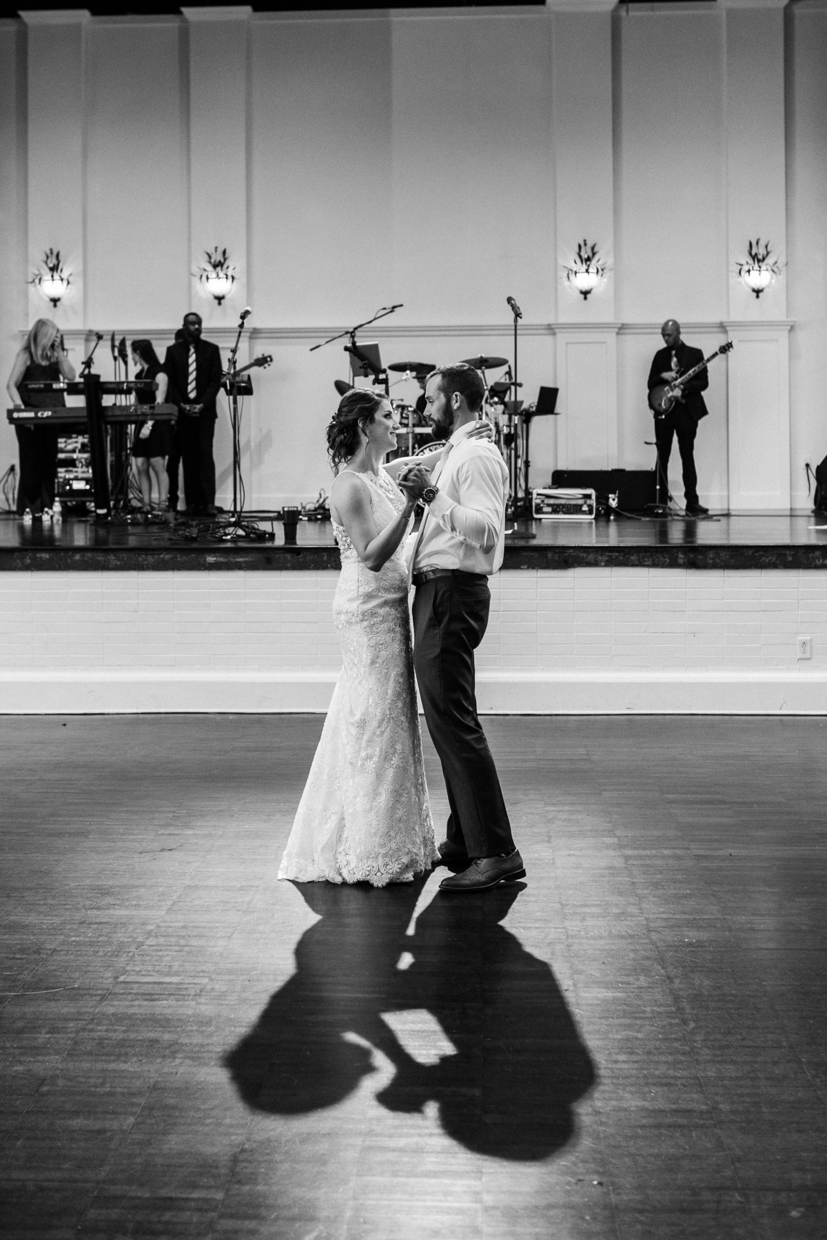 Black and white photo during a first dance with a band playing on stage