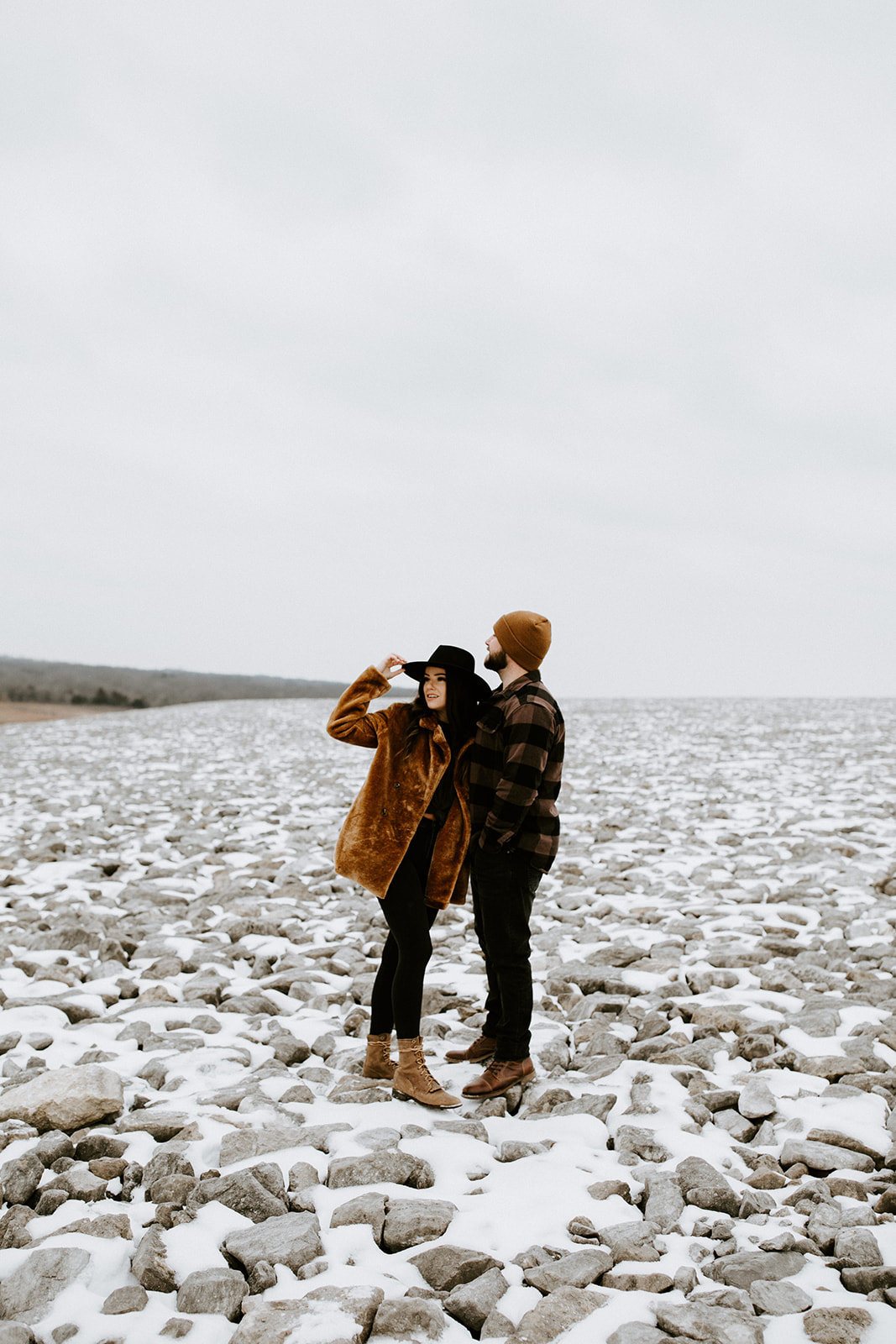 A couple in a snowy rock field look away.