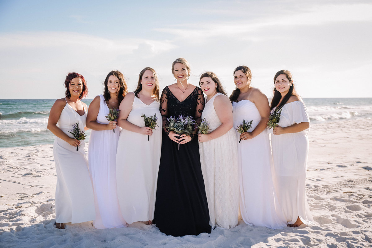 Bride in a black dress with bridesmaids in white dresses on the white sand beach in Pensacola, FL
