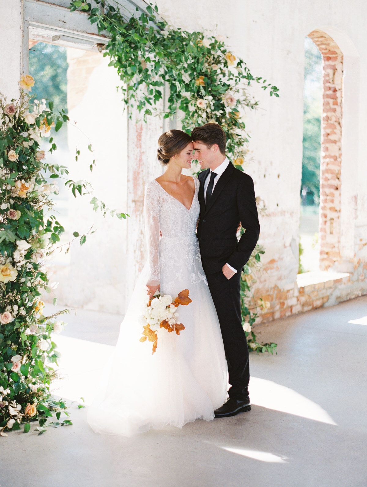 A North Carolina fine art film wedding photographer captures a couple posing during their fall Providence Cotton Mill wedding. As featured on Magnolia Rouge