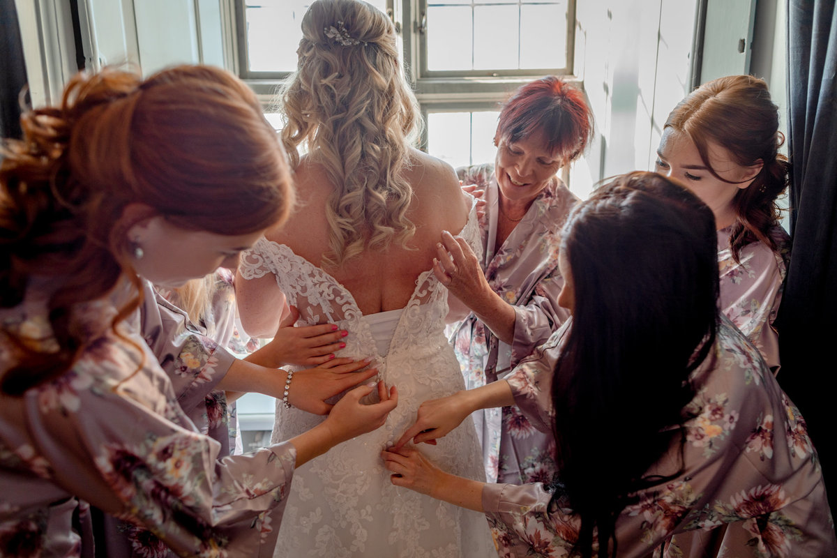 Bride by the window with the four bridesmaids helping her with her gown in the castleroom