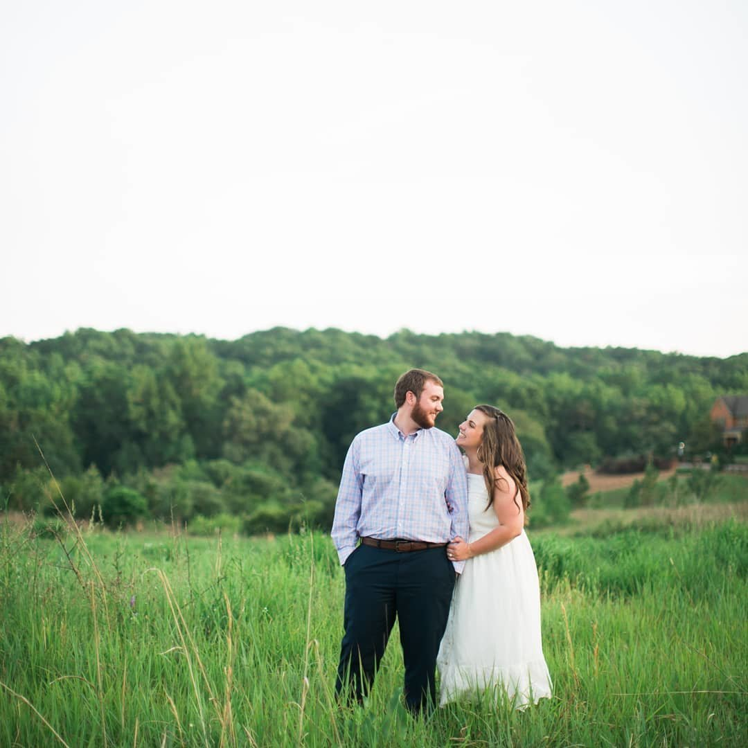 Wedding Photographer, couple standing together in tall grass looking at eachother