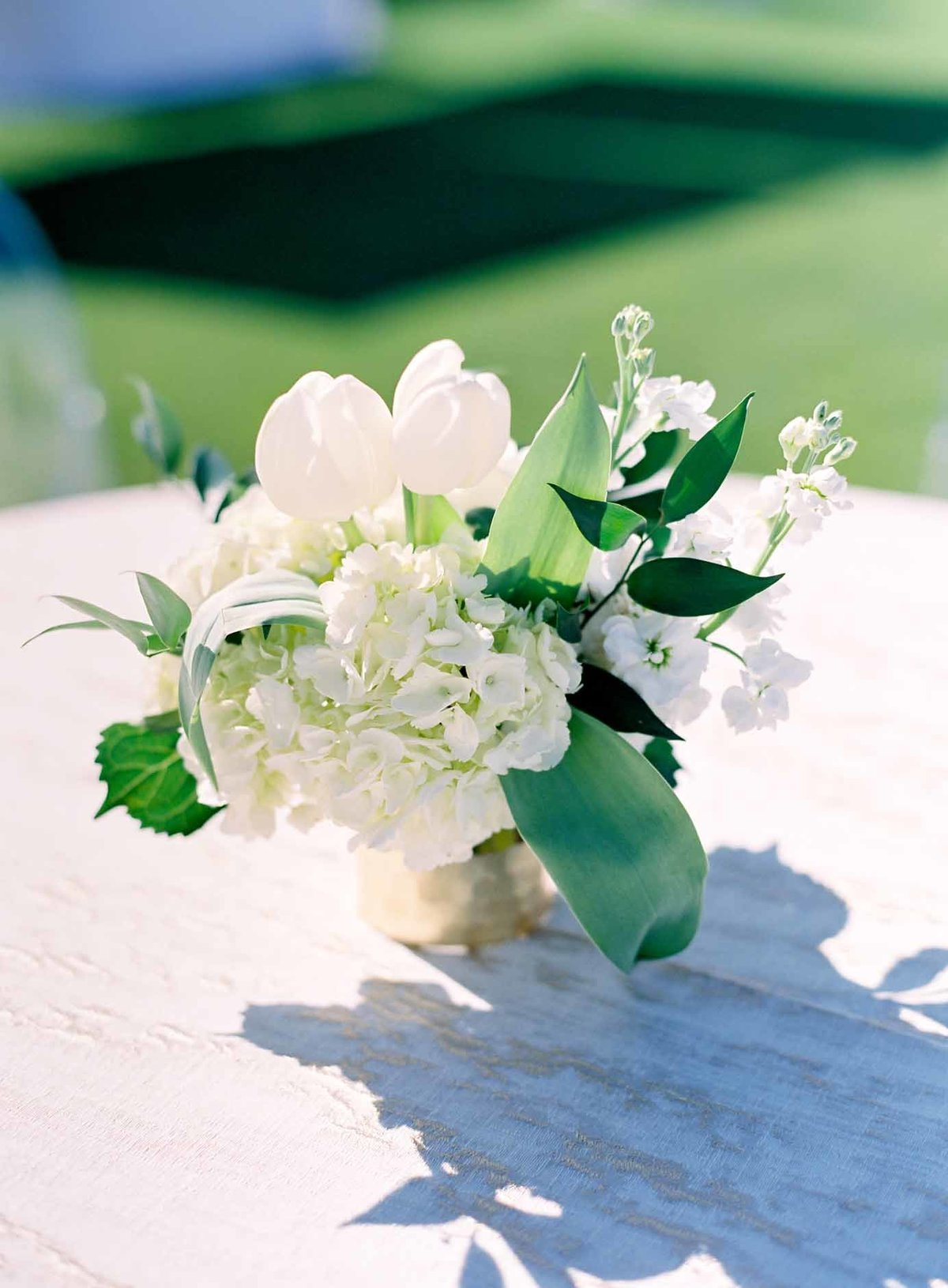 Beautiful outdoor wedding reception cocktail arrangement or white tulips hydrangea and stock.
