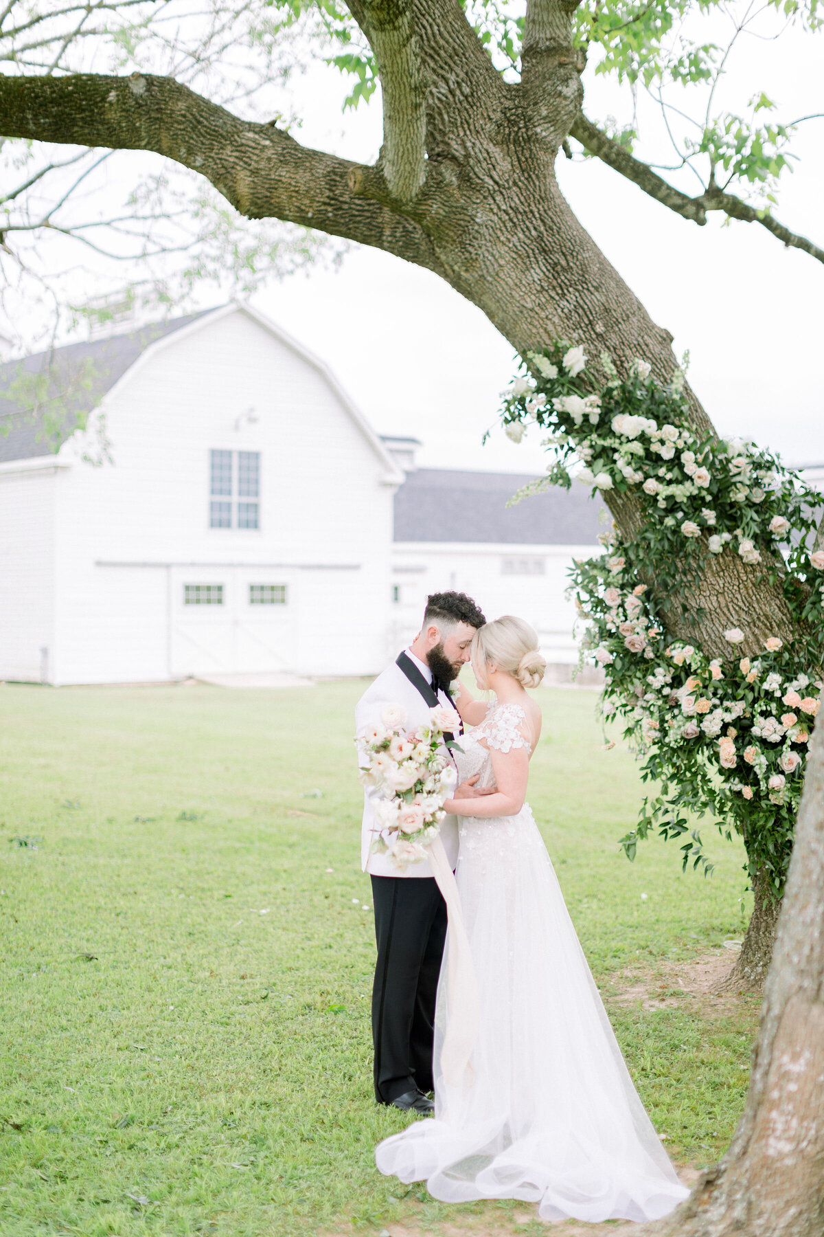 A gorgeous bride and groom standing in front of the Grand Texana's dairy barns. They are dressed in wedding attire with florals wrapping the trees behind them
