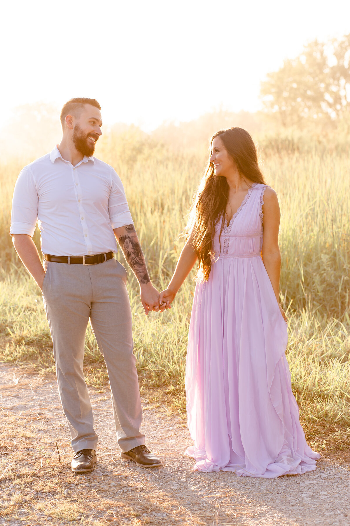 Summer Romantic Sunset Engagement Session guy and girl holding hands in lavender maxi dress in field on dirt road at Busch Wildlife in St. Louis by Amy Britton Photography Photographer in St. Louis
