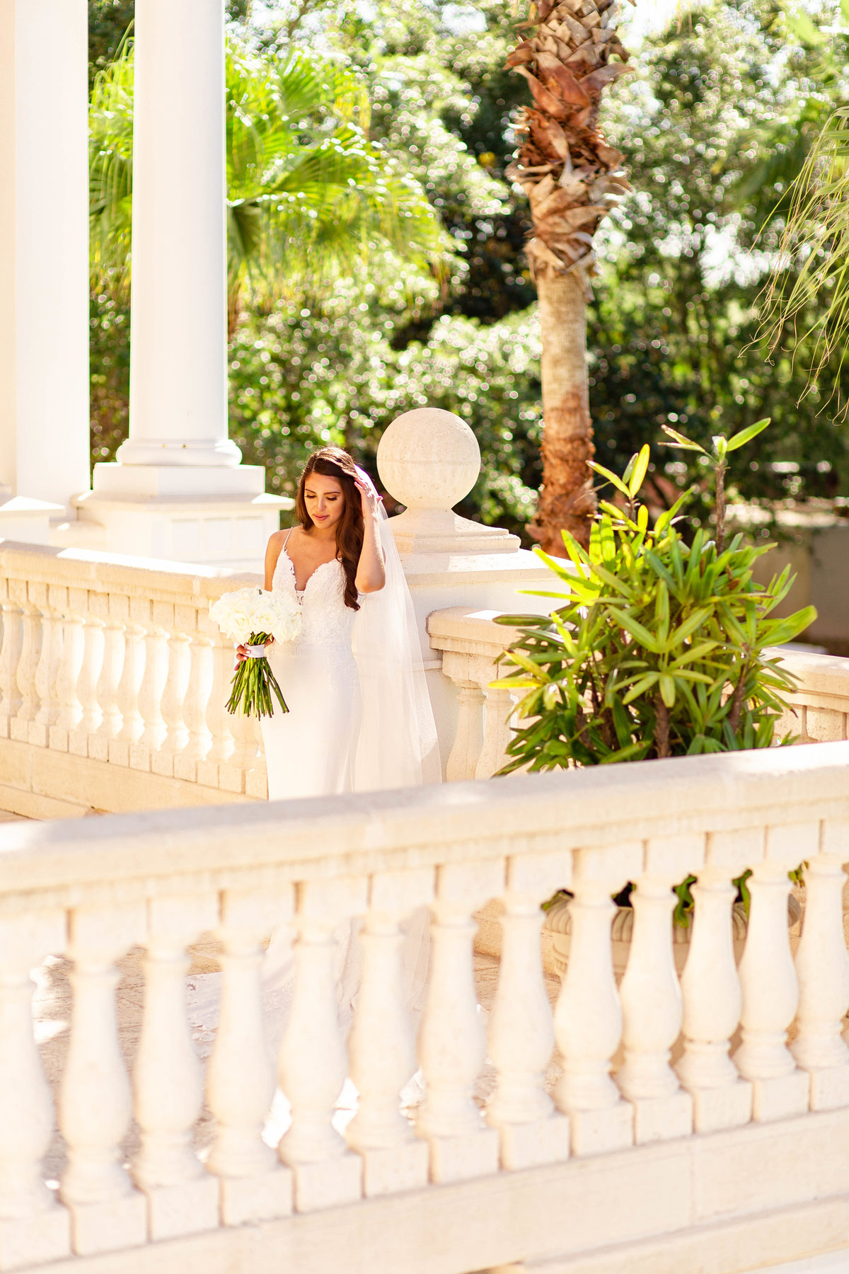 Bride in white wedding dress stands fixing her hair on her wedding day at wedding venue with marble flooring and white decor in Davenport, Florida