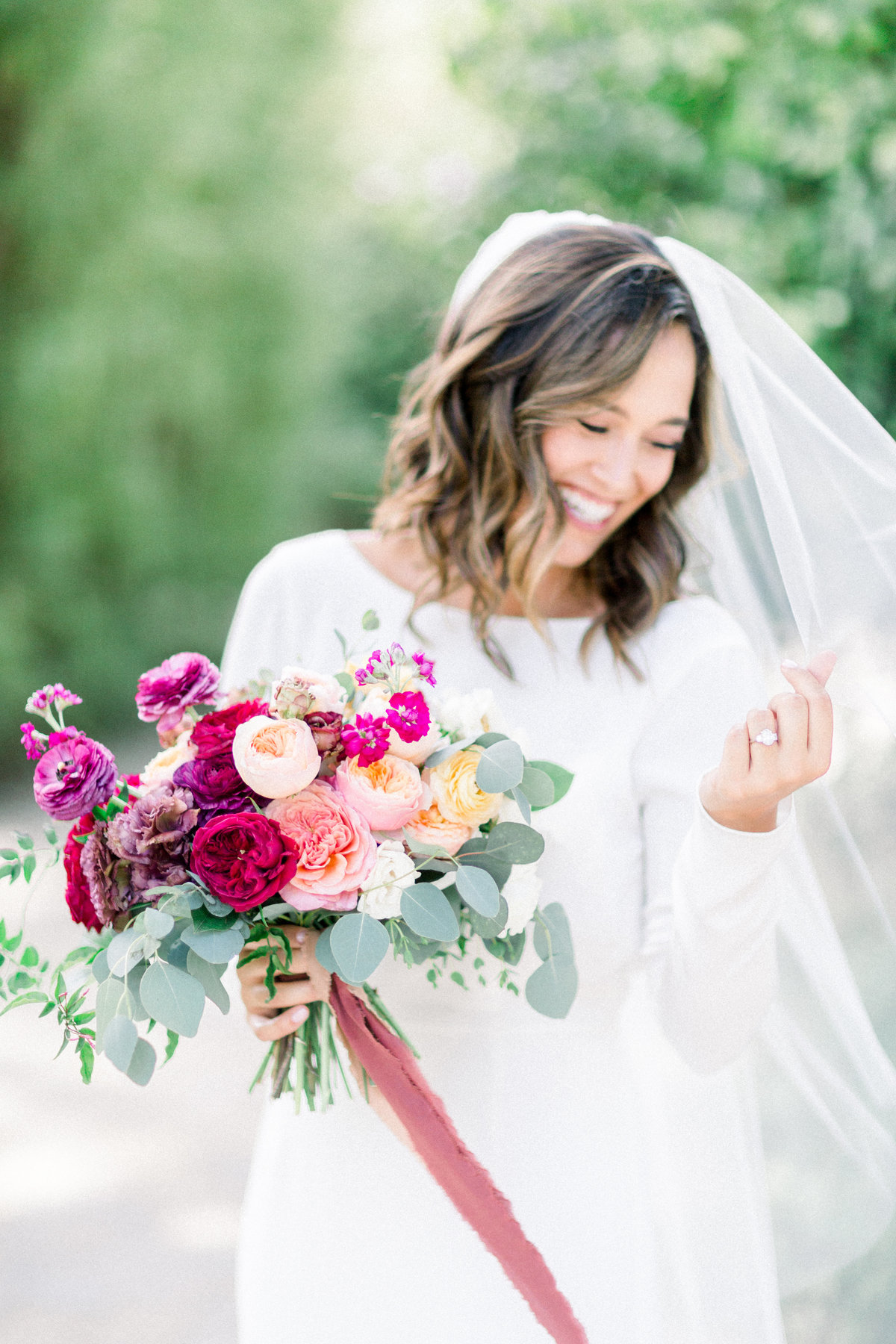 bride in long sleeve white wedding dress with veil and mauve bridal bouquet at Maravilla Gardens