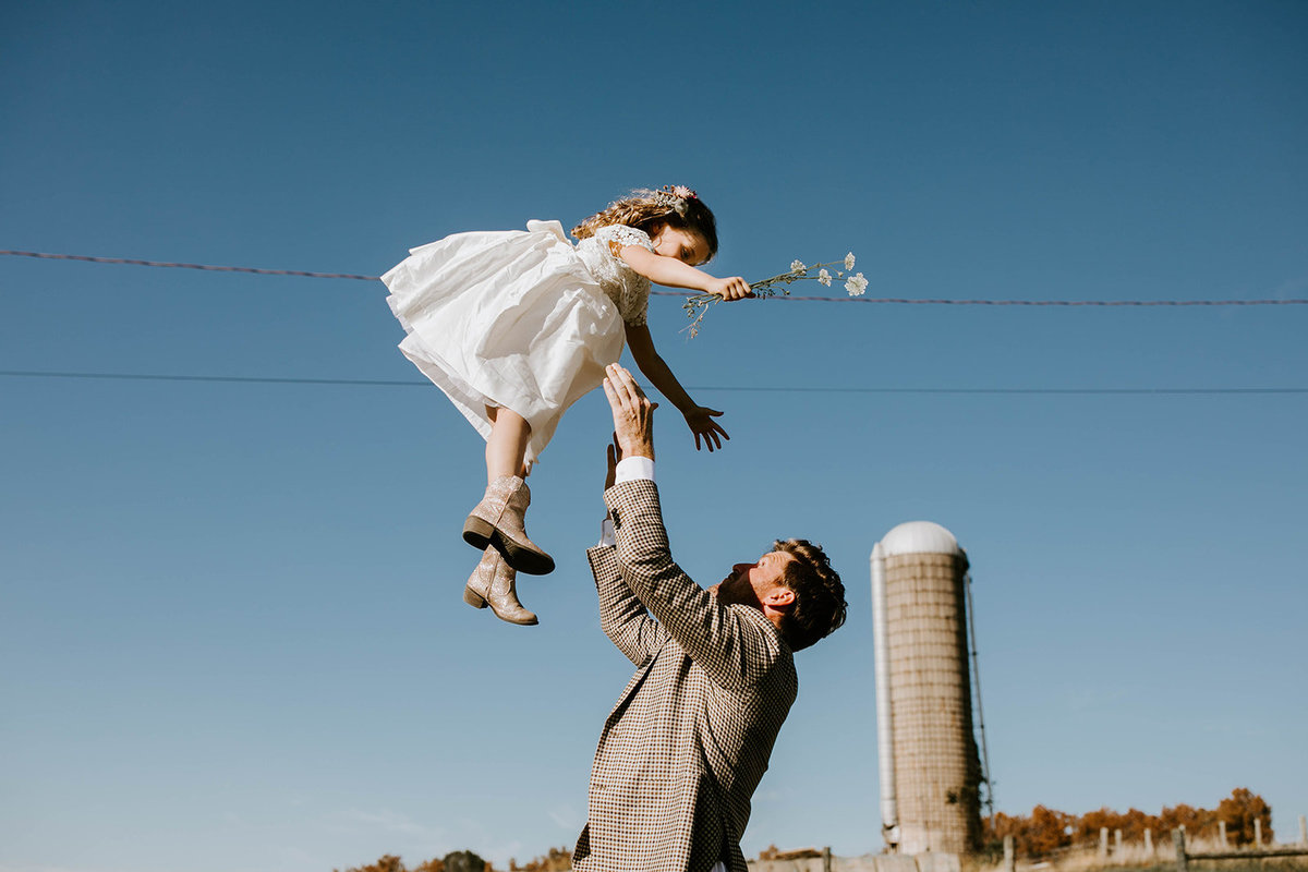 A groom throws a flower girl in the air.