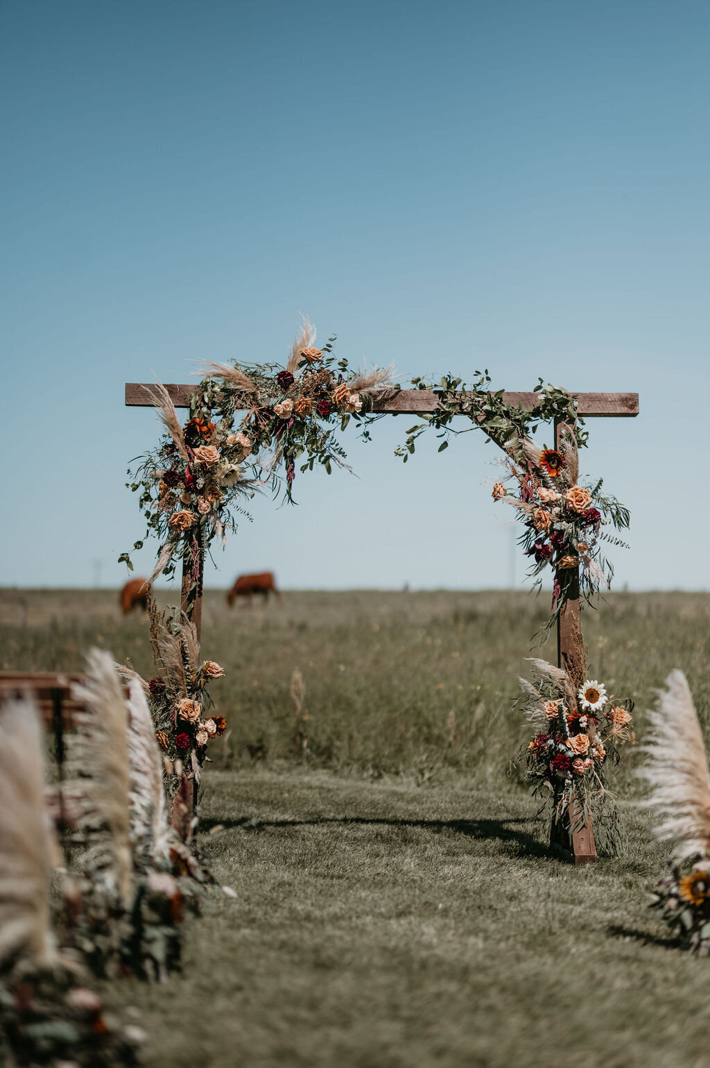 wood arbor in a prairie field, decorated with flowers