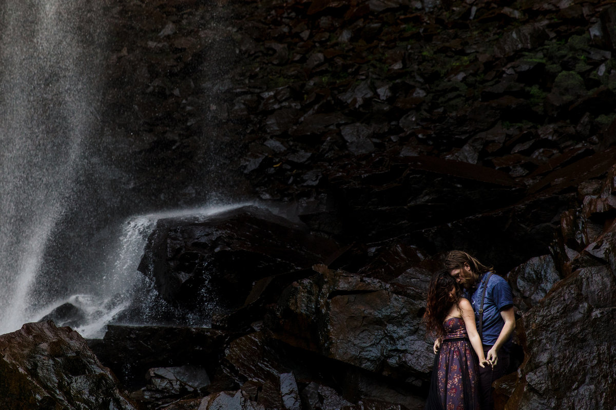 The couple hold each other with a waterfall backdrop in Maine