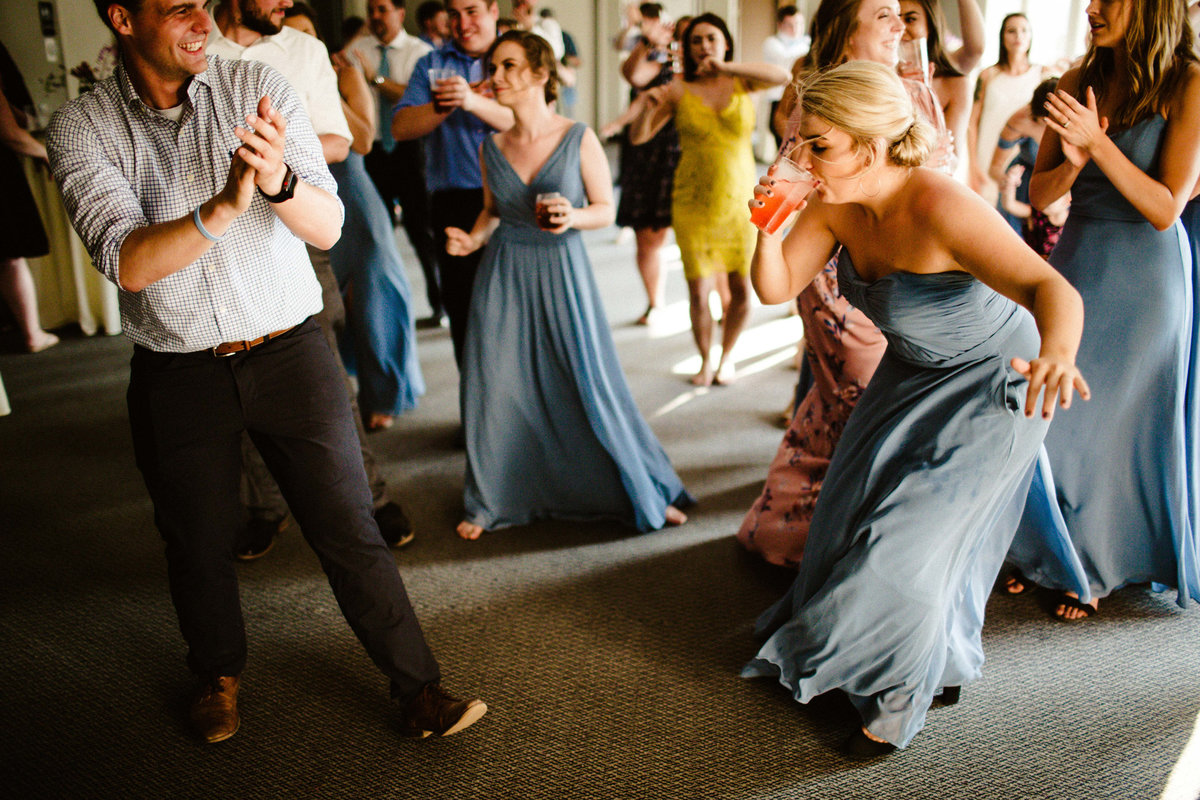 bridesmaid dances while taking a drink on dancefloor with dress blowing in wind