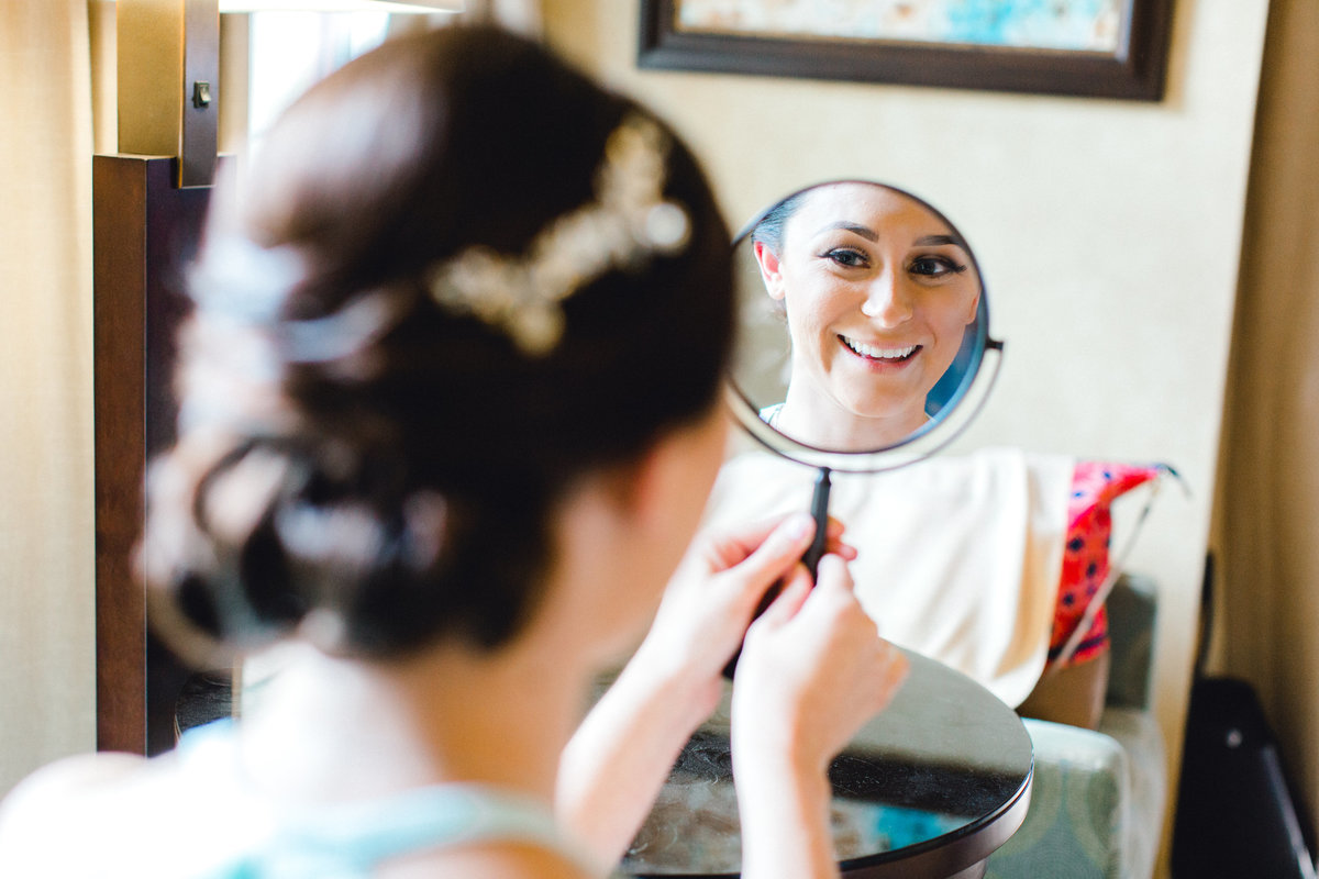 bride looking at her hair and makeup in the mirror for the first time at Vintners Inn in Santa Rosa California