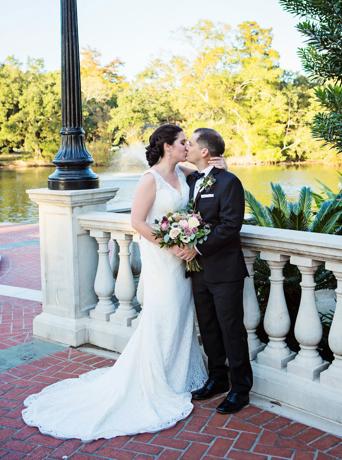 New orleans bride and groom kissing next to cement railing at Newman Bandstand