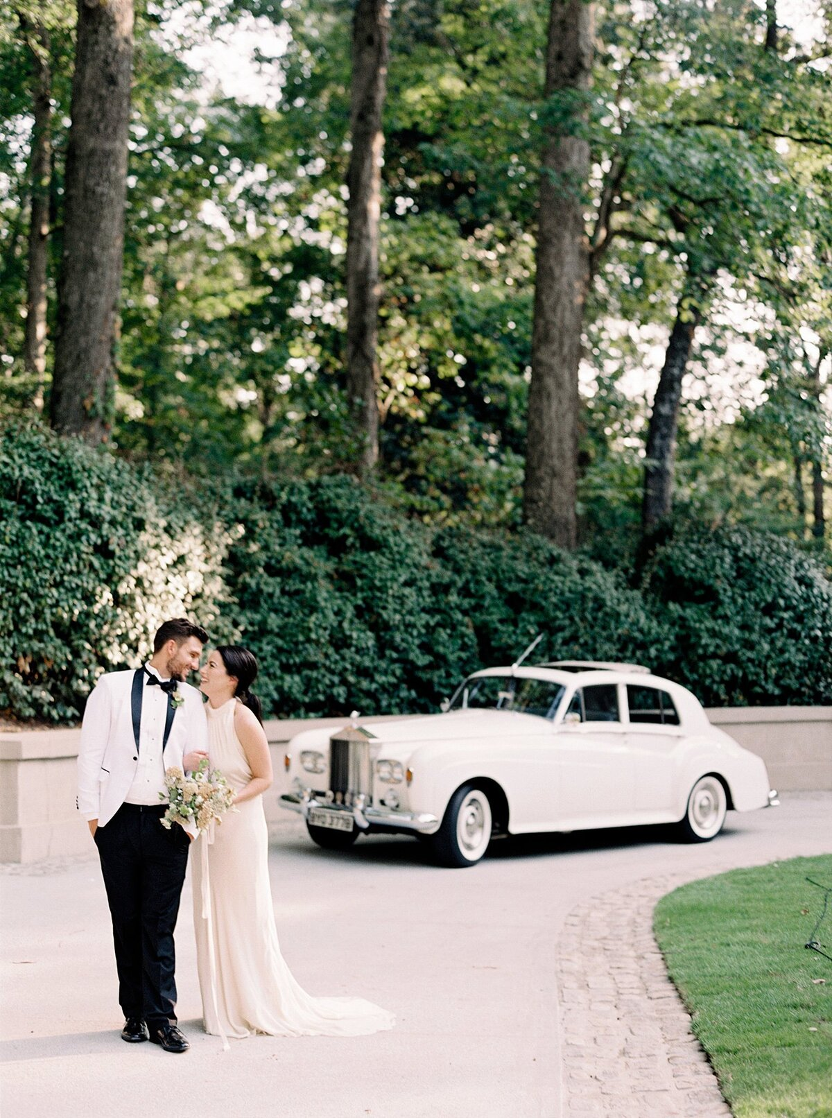 couple standing at a vintage car