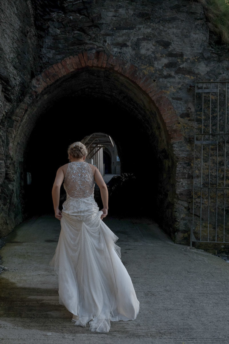 Bride in her wedding dress walking into the tunnel at Tunnels Beaches Devon