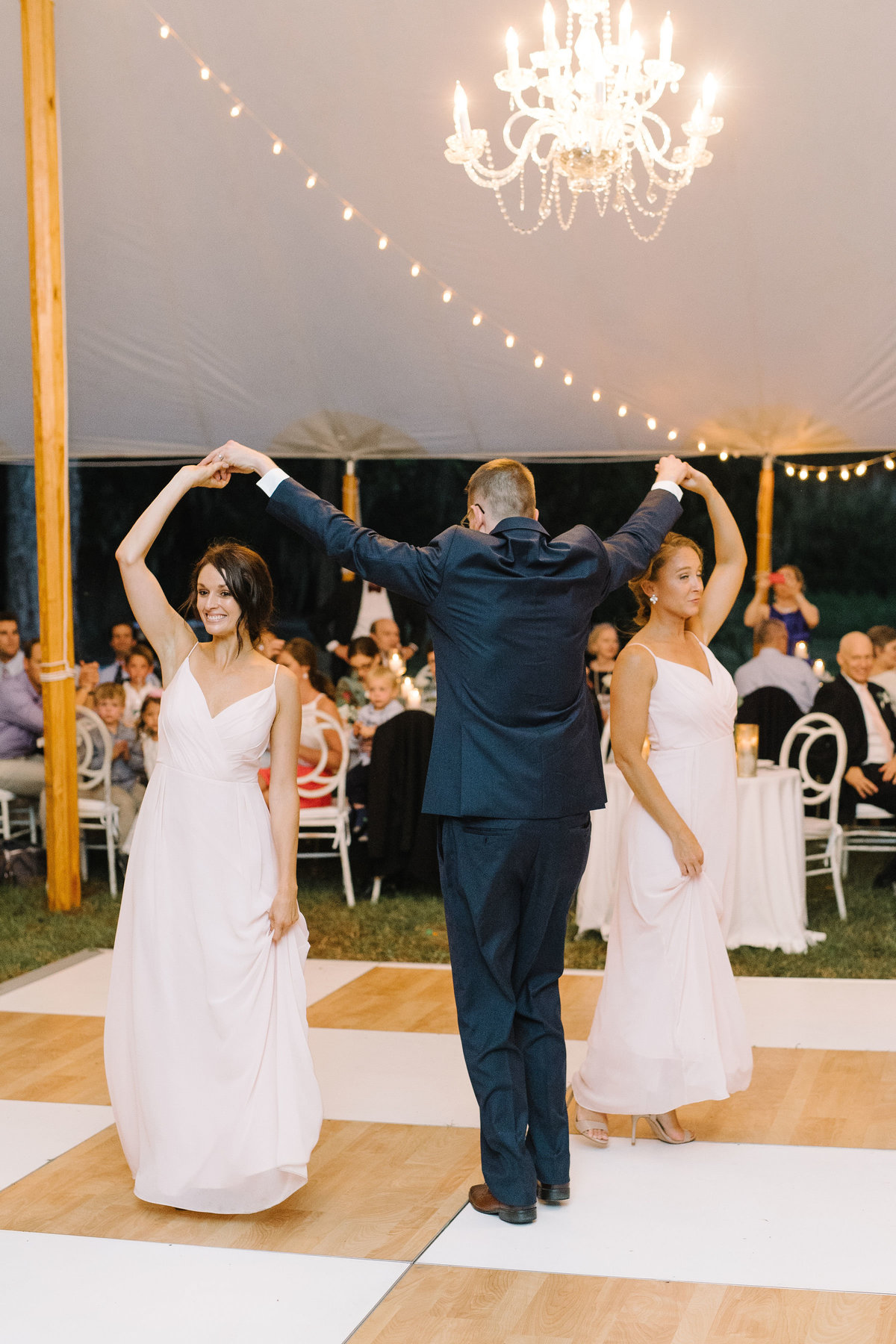Wedding Party on Birch Wood and White checkered Dance Floor under Sailcloth Tent with Cafe Lighting and Crystal Chandeliers