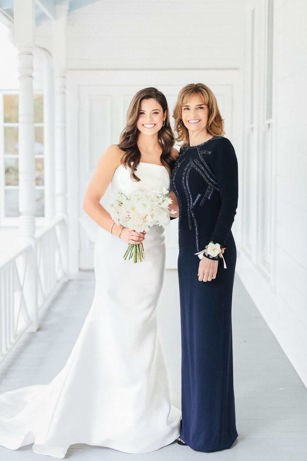 bride and mother in white wedding dress and blue gown posing for photo