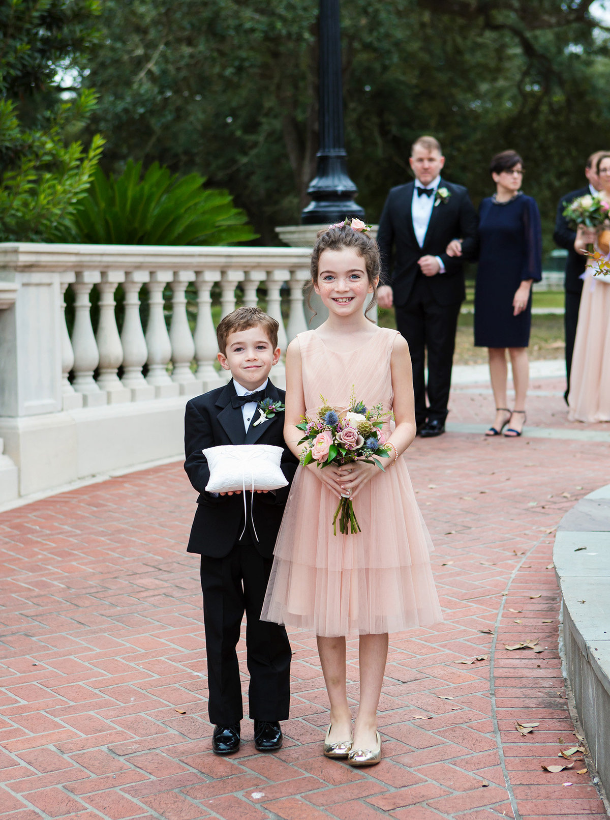 NOLA flower girl and ring bearer walking down cement pathway for wedding ceremony in Audubon Park