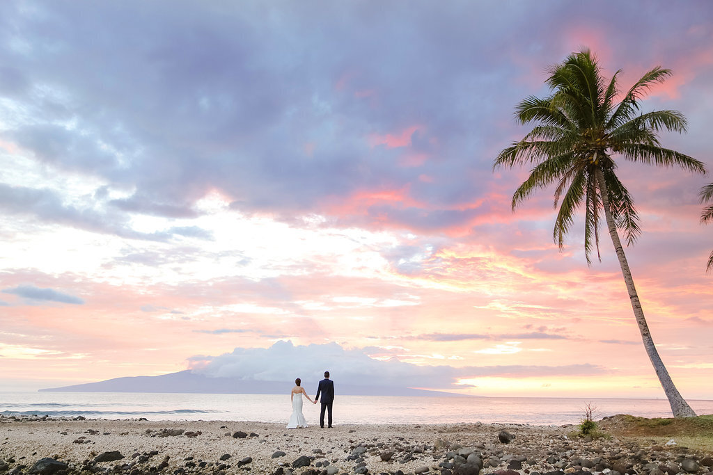 Bride and groom hold hands and watch the sunset after their wedding at Olowalu Plantation House on Maui