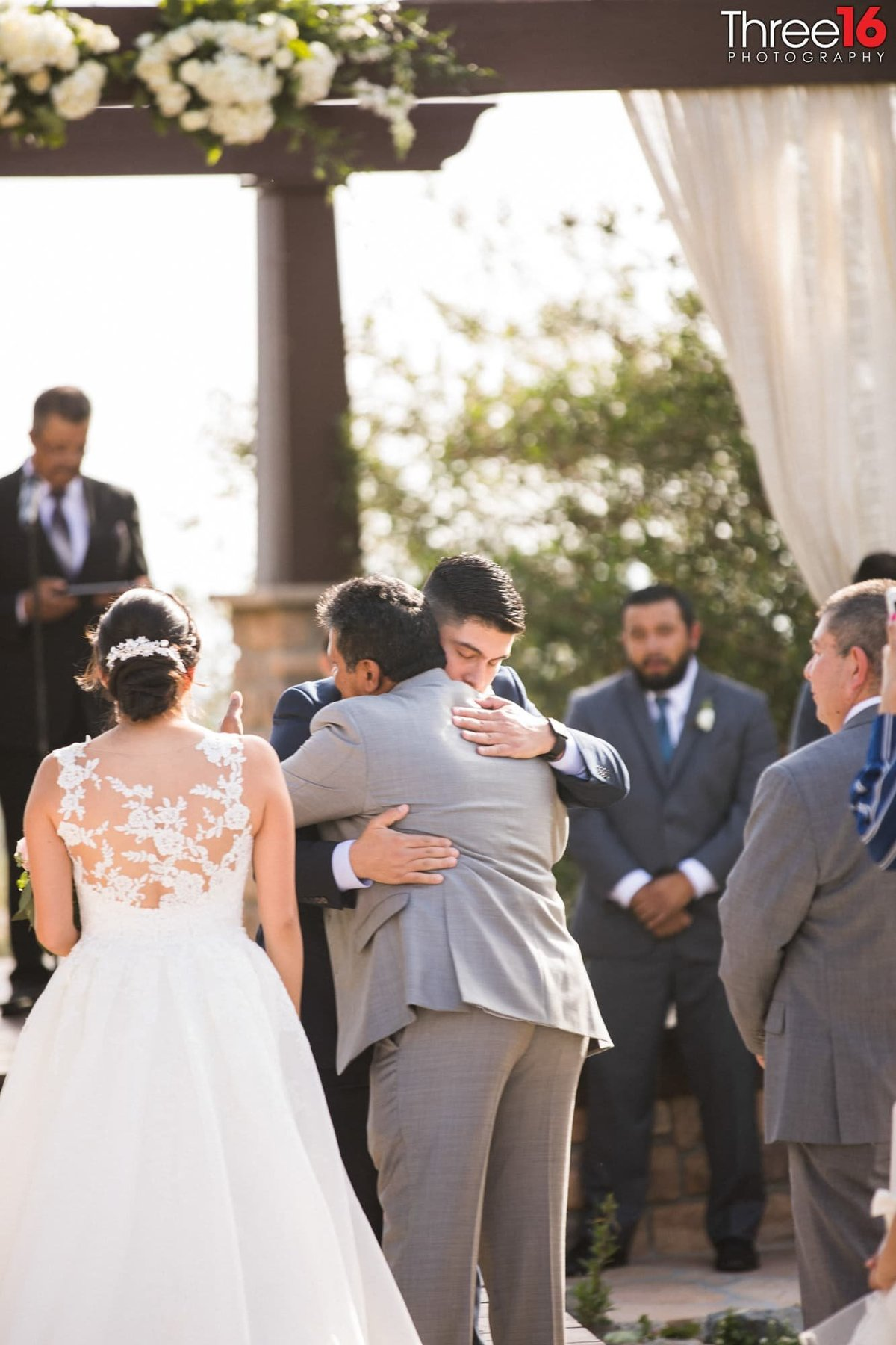 Father of the Bride hugs the Groom to be at the altar after handing his daughter to him