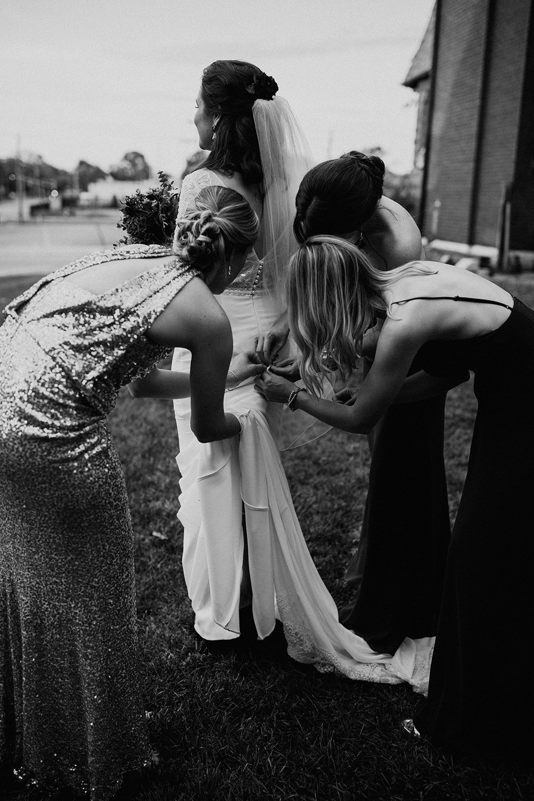 Three women bustle a bride's dress.
