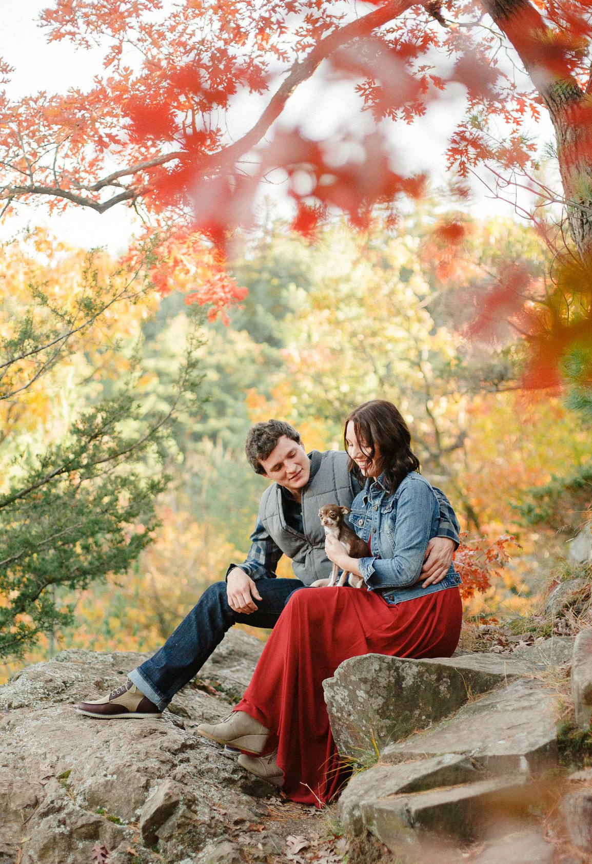 colored leaves of taylors falls state park with engaged couple and tiny dog