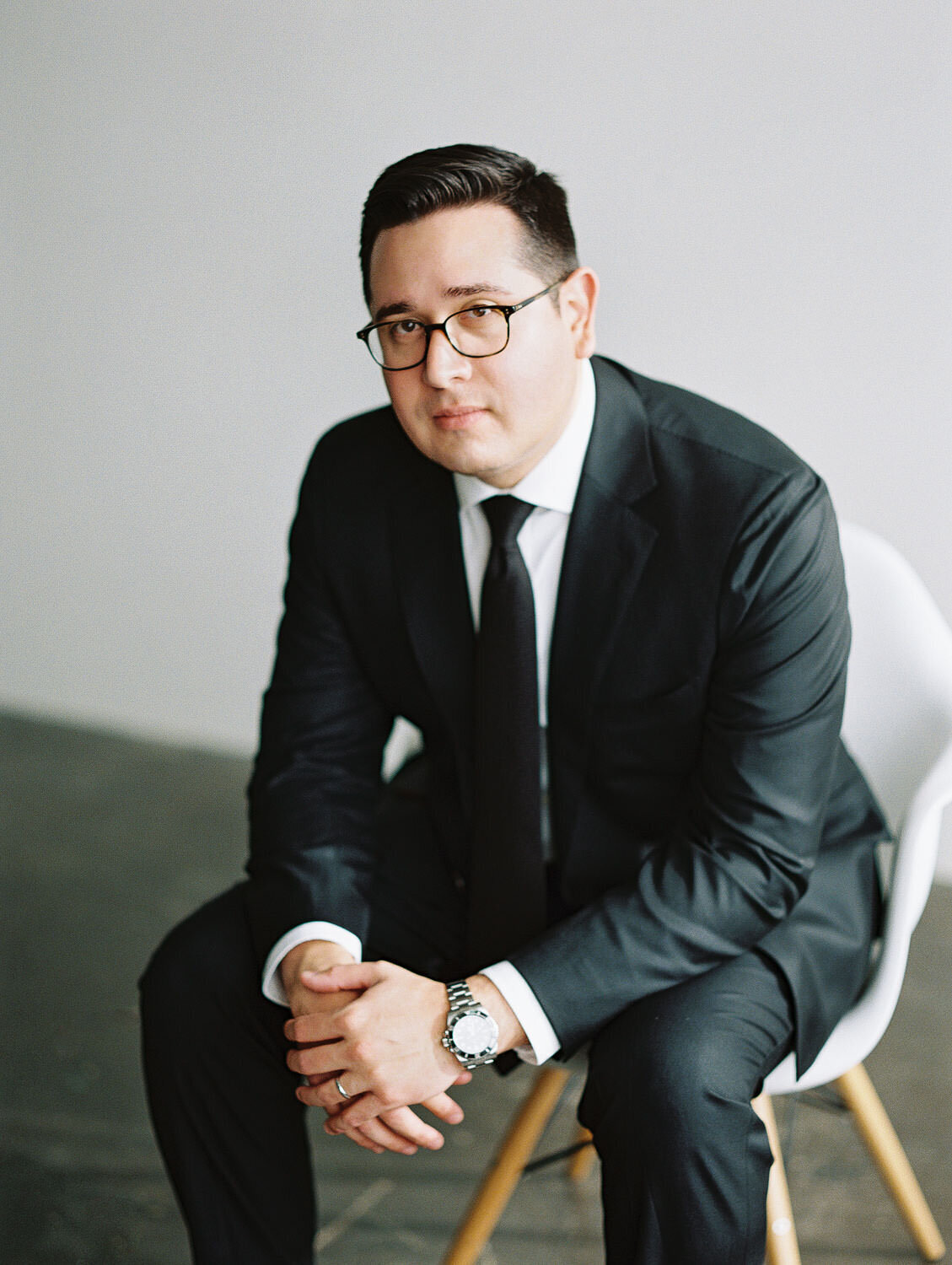 Man sitting in chair portrait black suit and glasses