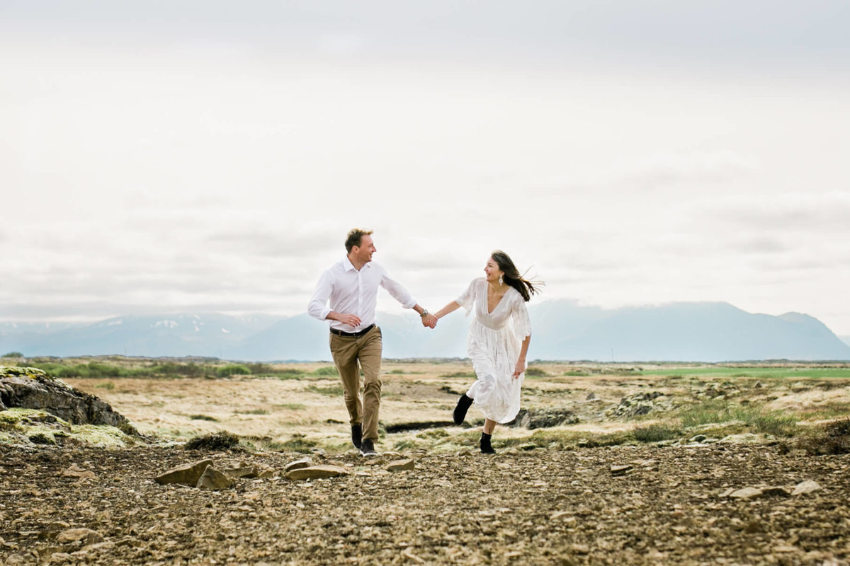 with the mountains behind them couple runs during their epic iceland elopement