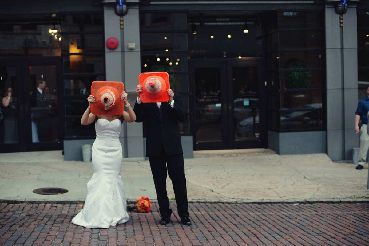 a silly bride and groom hold orange construction cones over their faces