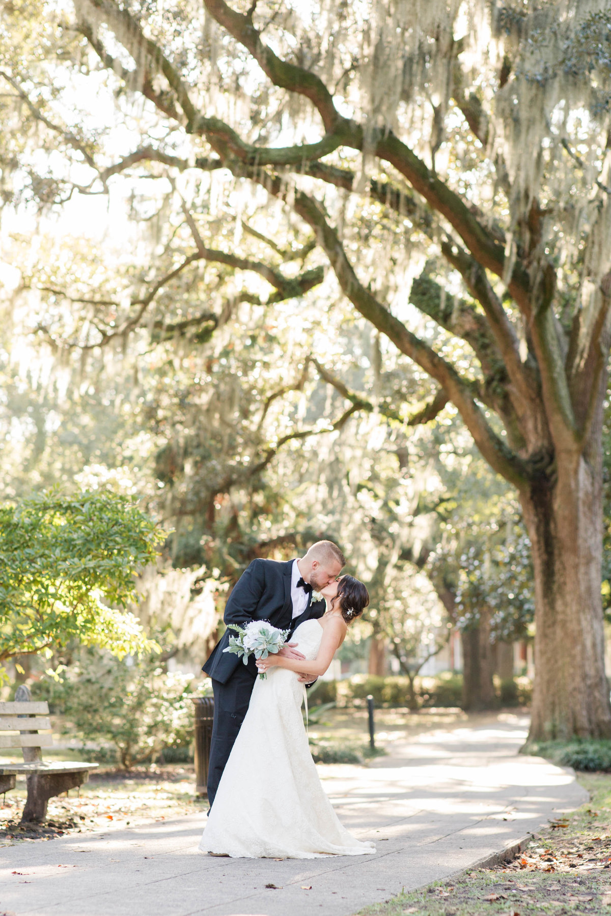groom dipping bride under huge oak trees in forsyth park savannah georgia