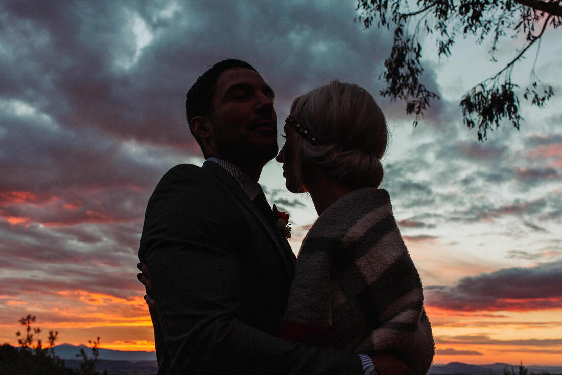 Bride & groom embrace during sunset after their backyard wedding in Yucaipa, Ca.